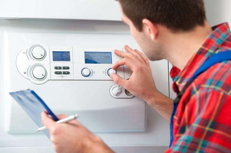 gas engineer testing boiler using dials