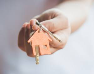 landlord holding out house heys with house keyring