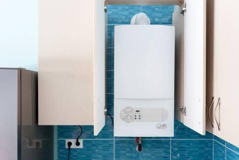 White gas boiler mounted in wall cupboard