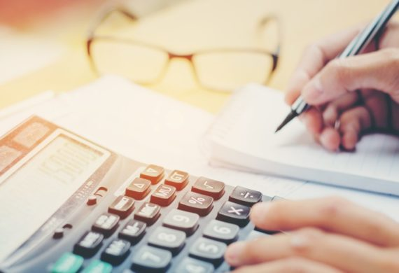 calculator and notepad with glasses working out finances