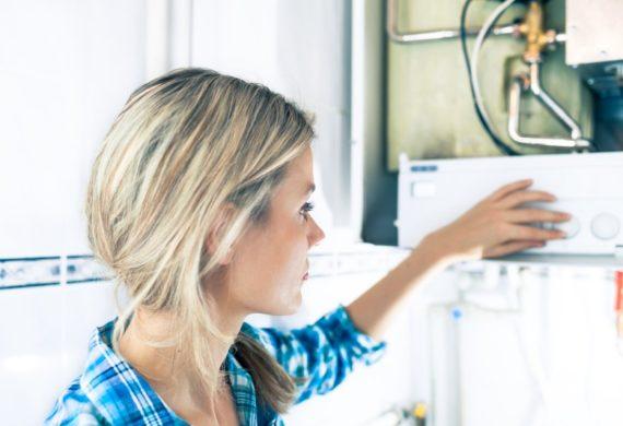 woman looking at broken down boiler using dials