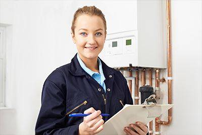 gas engineer smiling with clipboard in front of domestic boiler
