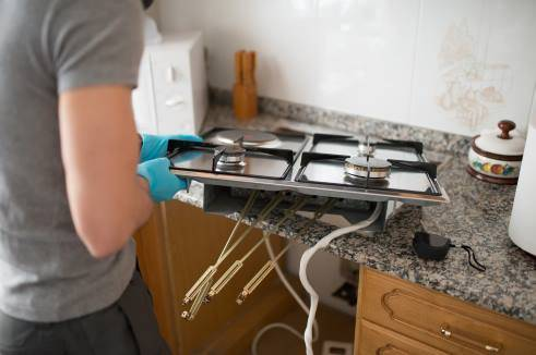 Man installing a gas hob in a kitchen.