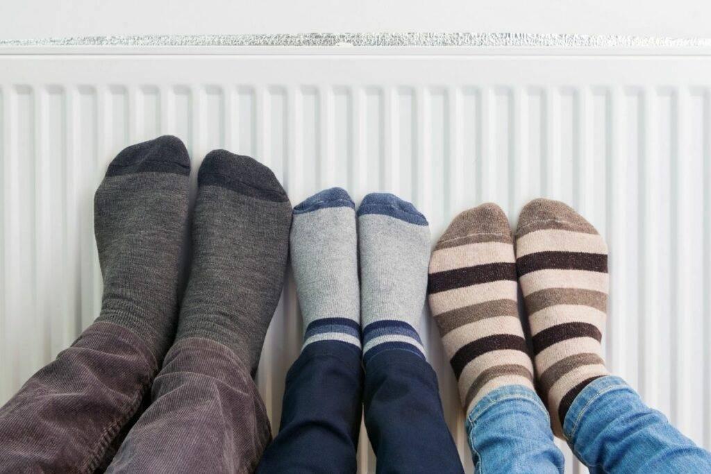 Feet in colourful socks on radiator for heat