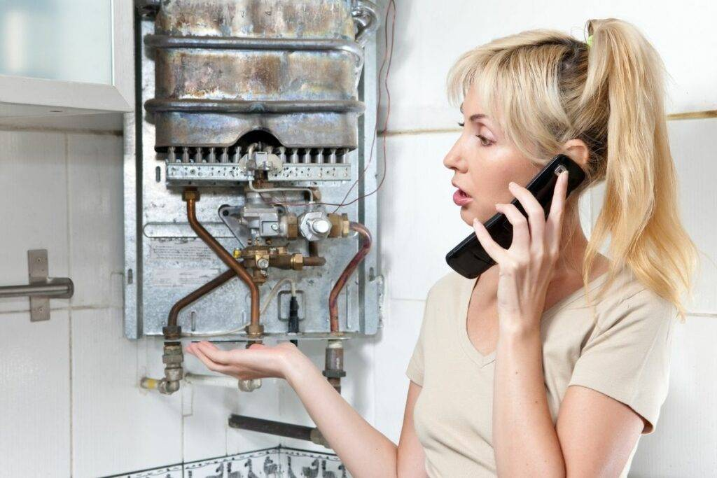 blonde lady on phone perplexed by boiler heater